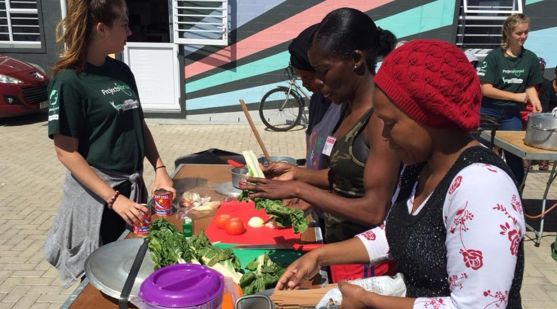 An intern on a nutritional internship in South Africa pictures a trio of women cooking healthy meals as part of a cooking competition.